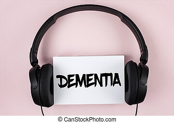 Handwriting text Dementia. Concept meaning Long term memory loss sign and symptoms made me retire sooner written on White Sticky Note paper on plain Pink background Headphone next to it.