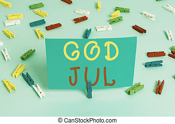 Handwriting text God Jul. Concept meaning Merry Christmas Greeting showing for new year happy holidays Colored clothespin papers empty reminder blue floor background office pin.
