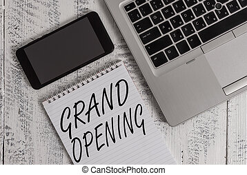 Handwriting text Grand Opening. Concept meaning Ribbon Cutting New Business First Official Day Launching Metallic laptop blank ruled notepad smartphone lying old wooden table.