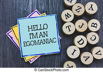 Handwriting text Hello I am An Egomaniac. Concept meaning Selfish Egocentric Narcissist Self-centered Ego Black wooden deck written sticky note beside some round woody alphabets.