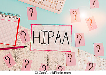 Handwriting text Hipaa. Conceptual photo Acronym stands for Health Insurance Portability Accountability Writing tools, computer stuff and scribbled paper on top of wooden table