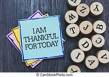 Handwriting text I Am Thankful For Today. Concept meaning Grateful about living one more day Philosophy Black wooden deck written sticky note beside some round woody alphabets.