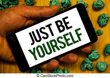 Handwriting text Just Be Yourself. Concept meaning Self Attitude Confidence True Confident Honesty Motivation Hand holding phone white screen written words crumbled green notes paper.