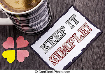 Handwriting text Keep It Simple Motivational Call. Concept meaning Simplify Things Easy Clear Concise Ideas written on Sticky Note Paper on the wooden background Coffee Cup and Heart next to it.