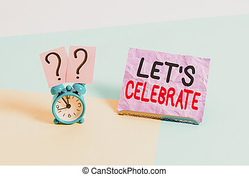 Handwriting text Let S Celebrate. Concept meaning party or other social event on a special day or occasion Mini size alarm clock beside a Paper sheet placed tilted on pastel backdrop.