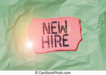 Handwriting text New Hire. Concept meaning someone who has not previously been employed by the organization Green crumpled ripped colored paper sheet centre torn colorful background.