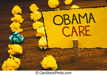 Handwriting text Obama Care. Concept meaning Government Program of Insurance System Patient ProtectionClothespin holding Yellow paper ideas crumpled papers wooden background.