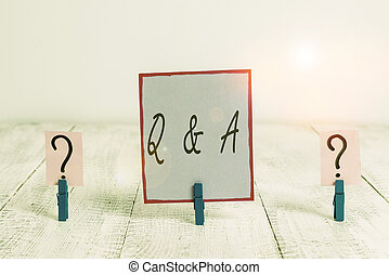 Handwriting text Q And A. Concept meaning defined as questions being asked and answers Scribbled and crumbling sheet with paper clips placed on the wooden table.
