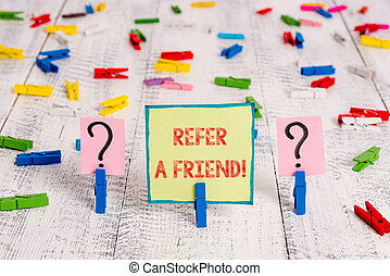 Handwriting text Refer A Friend. Concept meaning direct someone to another or send him something like gift Scribbled and crumbling sheet with paper clips placed on the wooden table.