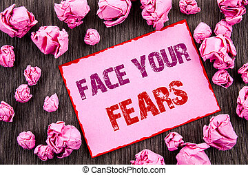 Handwriting text showing Face Your Fears. Business photo showcasing Challenge Fear Fourage Confidence Brave Bravery written on Pink Sticky Note Paper Folded Paper on wooden background
