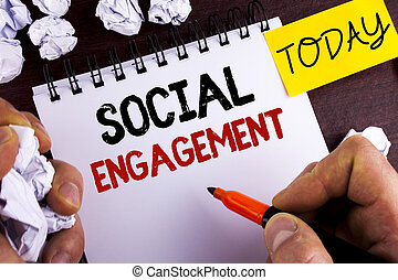 Handwriting text Social Engagement. Concept meaning post gets high reach Likes Ads SEO Advertising Marketing written by Man on Notepad on wooden background Today Paper Balls.