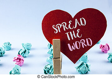 Handwriting text Spread The Word. Concept meaning Run advertisements to increase store sales many fold written on Red Paper Heart holding by Clip on plain background Paper Balls next to it.