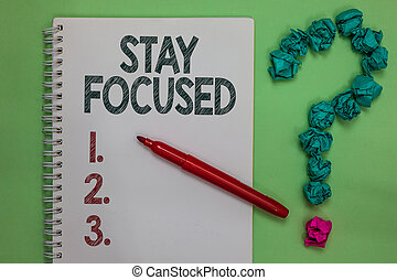 Handwriting text Stay Focused. Concept meaning Be attentive Concentrate Prioritize the task Avoid distractions Notebook marker crumpled papers forming question mark green background.