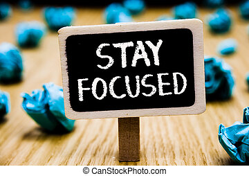Handwriting text Stay Focused. Concept meaning Be attentive Concentrate Prioritize the task Avoid distractions Blackboard crumpled papers several tries mistake not satisfied wooden floor.