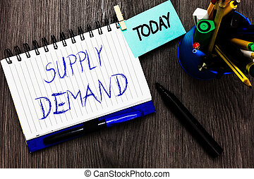 Handwriting text Supply Demand. Concept meaning Relationship between the amounts available and wanted Open notebook clothespin holding reminder cup markers wooden background.