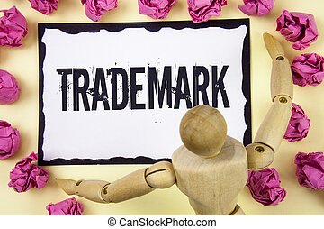 Handwriting text Trademark. Concept meaning Legally registered Copyright Intellectual Property Protection written on Sticky Note Paper within Paper Balls on plain background Wooden Robot Toy.