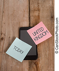 Handwriting text United Kingdom. Concept meaning Island country located off the northwestern coast of Europe Smartphone two colored sticky notes lying vintage old wooden background.