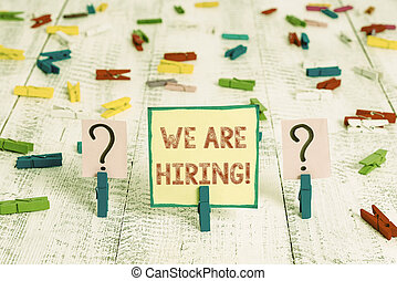 Handwriting text We Are Hiring. Concept meaning recently you employ someone or pay someone to do particular job Scribbled and crumbling sheet with paper clips placed on the wooden table.