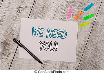 Handwriting text We Need You. Concept meaning asking someone to work together for certain job or target Plain note paper and line arrow stickers with pen above the wooden table.