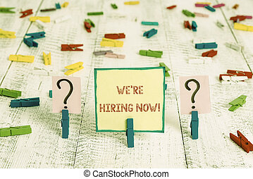 Handwriting text We Re Hiring Now. Concept meaning recently employ someone or pay someone to do particular job Scribbled and crumbling sheet with paper clips placed on the wooden table.