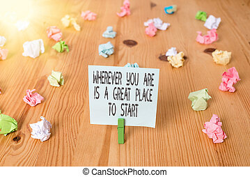 Handwriting text Wherever You Are Is A Great Place To Start. Concept meaning lot of success ahead of me Colored crumpled papers empty reminder wooden floor background clothespin.