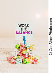 Handwriting text Work Life Balance. Concept meaning Division of time between working or family and leisure Reminder pile colored crumpled paper clothespin reminder white wooden space.