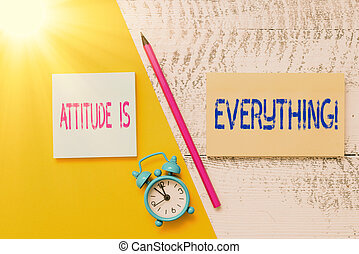 Handwriting text writing Attitude Is Everything. Concept meaning Personal Outlook Perspective Orientation Behavior Notepads marker pen colored paper sheet alarm clock wooden background.