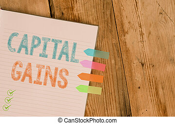 Handwriting text writing Capital Gains. Concept meaning Bonds Shares Stocks Profit Income Tax Investment Funds Striped note book four colored arrow banners reminder wooden background.