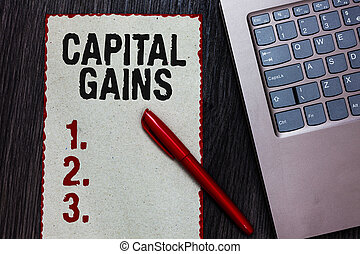 Handwriting text writing Capital Gains. Concept meaning Bonds Shares Stocks Profit Income Tax Investment Funds Piece paper red borders black marker computer keyboard wooden background.