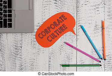 Handwriting text writing Corporate Culture. Conceptual photo pervasive values and attitudes that characterize a company Open laptop blank speech bubble pens ballpoints lying vintage wooden table