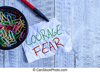 Handwriting text writing Courage Fear. Concept meaning quality of mind that enables a demonstrating to face difficulty Wrinkle paper and notebook plus stationary placed above wooden background.