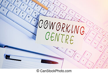 Handwriting text writing Coworking Centre. Concept meaning shared workplace often office and independent activity White keyboard with note paper and clips on white background.