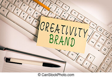 Handwriting text writing Creativity Brand. Concept meaning design name or feature that distinguishes organization White keyboard with note paper and clips on white background.