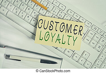 Handwriting text writing Customer Loyalty. Concept meaning result of consistently positive emotional experience White keyboard with note paper and clips on white background.
