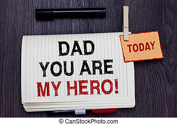 Handwriting text writing Dad You Are My Hero. Concept meaning Admiration for your father love feelings compliment Written paper on wooden desk paper clip grip note with red words black pen.