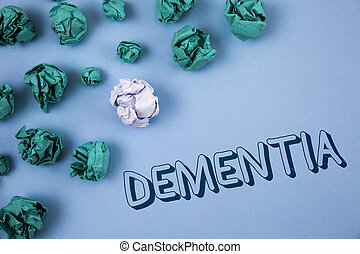 Handwriting text writing Dementia. Concept meaning Long term memory loss sign and symptoms made me retire sooner written on Plain Blue background Crumpled Paper Balls next to it.
