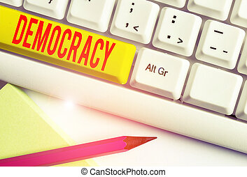 Handwriting text writing Democracy. Concept meaning freedom of the showing to express their feelings and beliefs White pc keyboard with empty note paper above white background key copy space.
