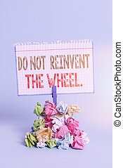 Handwriting text writing Do Not Reinvent The Wheel. Concept meaning stop duplicating a basic method previously done Reminder pile colored crumpled paper clothespin reminder blue background.