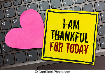 Handwriting text writing I Am Thankful For Today. Concept meaning Grateful about living one more day Philosophy Written on black bordered yellow page touched pink heart on computer keyboard.