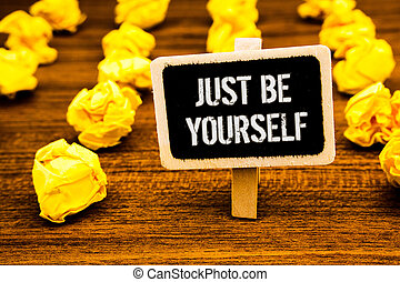 Handwriting text writing Just Be Yourself. Concept meaning Self Attitude Confidence True Confident Honesty Motivation White text black paint wooden board clip desk yellow paper notes warning.