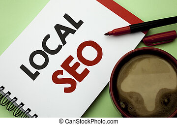 Handwriting text writing Local Seo. Concept meaning Search Engine Optimization Strategy Optimize Local Find Keywords written on Notebook Book on the plain background Coffee Cup next to it.