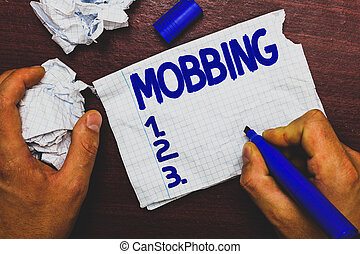 Handwriting text writing Mobbing. Concept meaning Bulling of individual specially at work Emotional abuse Stress Man holding marker notebook page crumpled papers several tries mistakes.