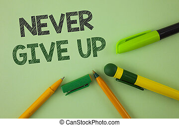 Handwriting text writing Never Give Up. Concept meaning Be persistent motivate yourself succeed never look back written on Plain Green background Pens next to it.