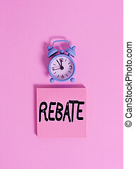 Handwriting text writing Rebate. Conceptual photo Huge rewards that can get when you engaged to a special promo Vintage alarm clock wakeup blank notepad sticky note colored background