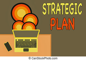 Handwriting text writing Strategic Plan. Concept meaning a systematic process of envisioning a desired future Upper view office working place laptop lying wooden desk smartphone side.