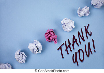 Handwriting text writing Thank You Motivational Call. Concept meaning Appreciation greeting Acknowledgment Gratitude written on Plain Blue background Crumpled Paper Balls next to it.