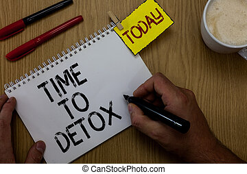 Handwriting text writing Time To Detox. Concept meaning Moment for Diet Nutrition health Addiction treatment cleanse Man holding marker notebook clothespin reminder wooden table cup coffee.