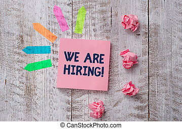 Handwriting text writing We Are Hiring. Concept meaning recently you employ someone or pay someone to do particular job Plain note paper and line arrow stickers on the top of wooden table desk.