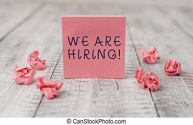 Handwriting text writing We Are Hiring. Concept meaning recently you employ someone or pay someone to do particular job Thick set of plain note paper with scraps on the wooden textured table.