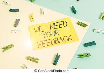 Handwriting text writing We Need Your Feedback. Concept meaning Give us your review thoughts comments what to improve Colored clothespin paper empty reminder yellow blue floor background office.
